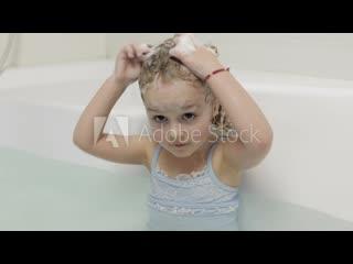 Четырёхлетняя девушка ребёнок мылит волосы в ванной